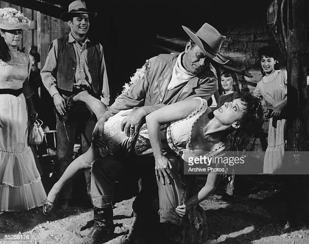 American actor John Wayne gives Maureen O'Hara a public spanking in the film 'McLintock' watched by Stefanie Powers his onscreen daughter and Patrick...
