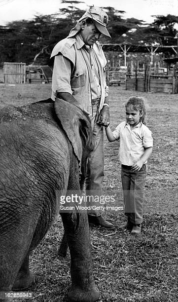 American actor John Wayne holds the hand on a young girl as he introduces her to a baby elephant during the filming of 'Hatari' Tanzania 1962