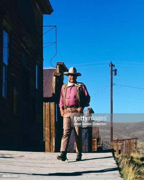 American actor John Wayne in costume walks on the set of 'Rio Lobo' 1970