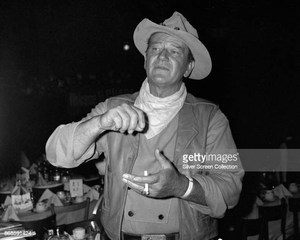American actor John Wayne , in western clothing, holds a cigarette at an unspecified dinner event, 1960s.