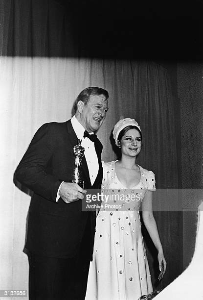 American actor John Wayne poses with presenter American singer and actress Barbra Streisand at the Academy Awards, Los Angeles, California, April 7,...