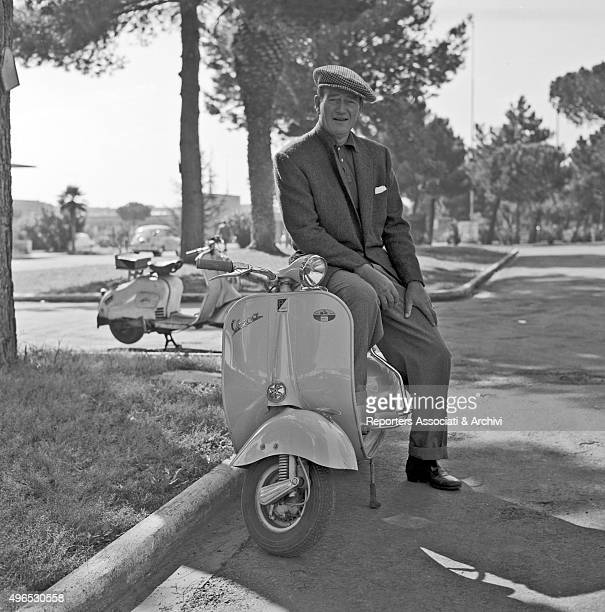 American actor John Wayne posing in the streets of the city on a Vespa Rome 1957