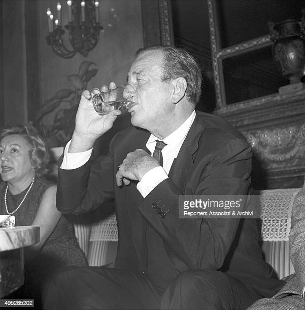 American actor John Wayne releasing a press conference in a hotel in Rome He's sitting and drinking a glass Rome 1959