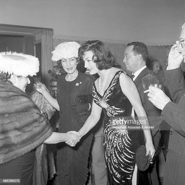 American actor John Wayne 's wife Pilar Pallete shaking a woman's hand at the cocktail for the end of the shooting of the film Legend of the Lost 1957
