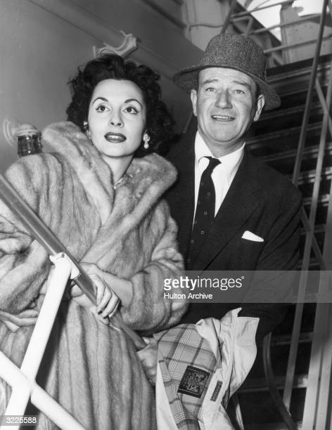 American actor John Wayne sets sail with his wife Pilar Palette for Tripoli Lebanon to star in director Henry Hathaway's film 'Legend of the Lost'