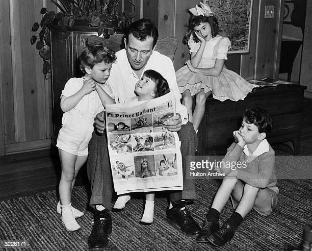 American actor John Wayne sitting on a chair and reading a Prince Valiant comic with his four children Hollywood California From left Patrick Melinda...