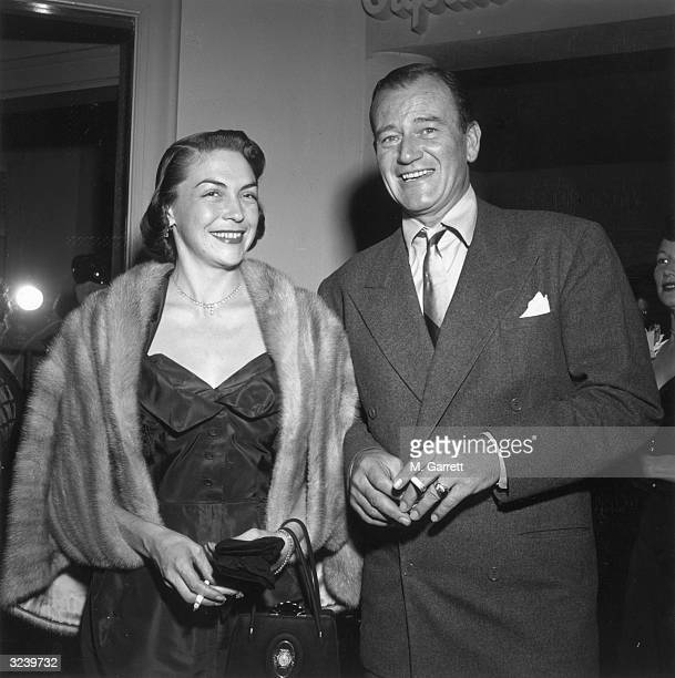American actor John Wayne smiles with his second wife Esperanza Bauer while attending a party for American comedian Red Skelton's television debut...