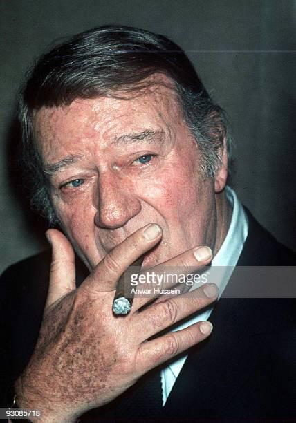 American actor John Wayne smokes a cigar circa 1979 in London England