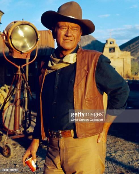 American actor John Wayne stands by a lighting rig on the set of 'El Dorado' , 1967.