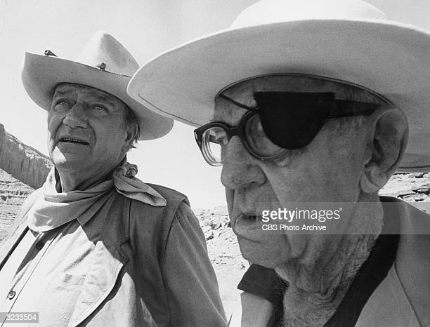 American actor John Wayne stands to the left of American film director John Ford on a western landscape from the CBS television special 'The American...