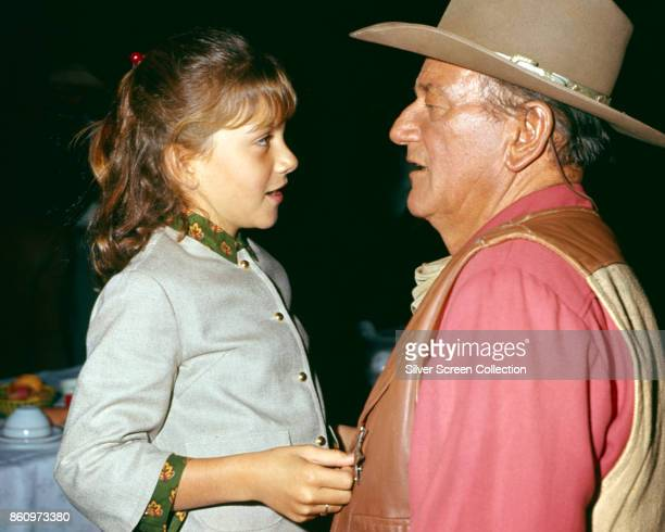 American actor John Wayne talks with his daughter Aissa in an unspecified restaurant, 1967. Wayne is in costume for his role in 'El Dorado' .