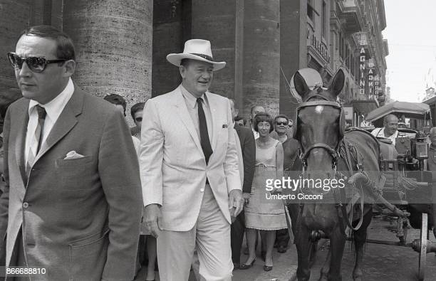 American actor John Wayne walking in the city center in Rome with a big hat on his head and close to a typical Italian carriage He is followed by...