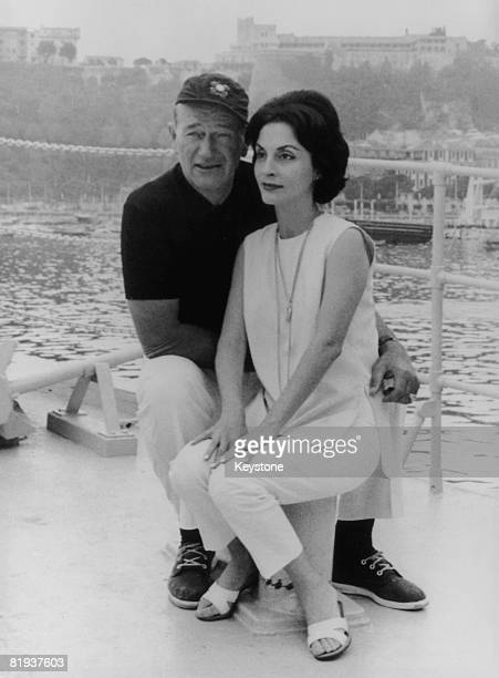 American actor John Wayne with his wife Pilar on board their yacht 'The Wild Goose' at Monte Carlo following a transatlantic crossing 26th August 1963