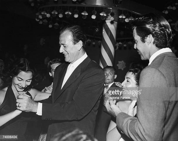 American actor John Wayne with his wife Pilar Palette and actor Rory Calhoun with his wife Lita Baron at the Mocambo nightclub in West Hollywood...