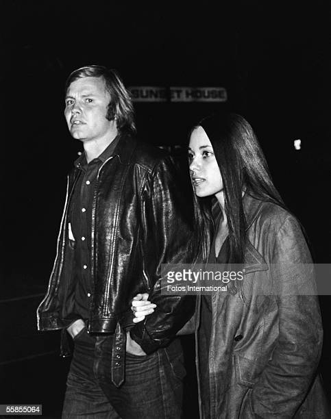 American actor Jon Voight and his second wife Marcheline Bertrand walk handonarm along a street at night in front of a sign which reads 'Sunset...