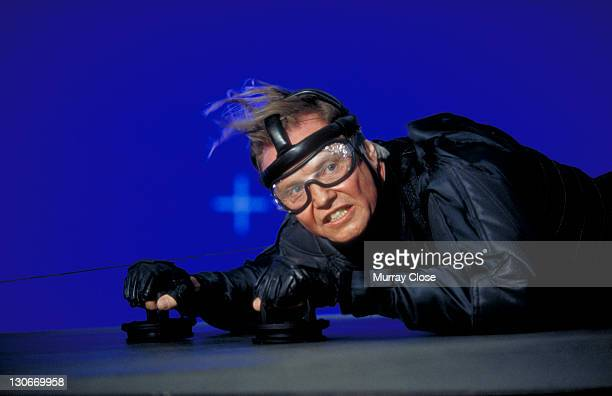 American actor Jon Voight as Jim Phelps during the making of the film 'Mission Impossible' 1996 In this scene he uses magnetic cups to cling to a...