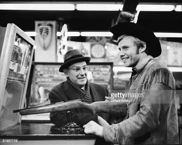 American actor Jon Voight talks to an unidentified actor at an arcade in a still from the film 'Midnight Cowboy,' directed by John Schlesinger, 1969.