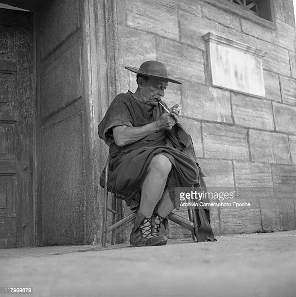 American actor Joseph 'Buster' Keaton wearing a Roman armour and lighting a cigarette resting on a chair during the shooting of ' A Funny Thing...