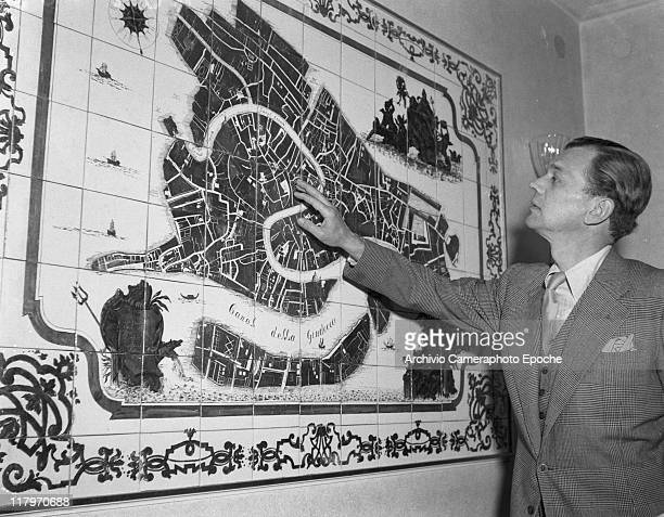American actor Joseph Cotten wearing a plaid blazer a plaid waistcoat and a tie pointing a tile map of Venice Venice 1949