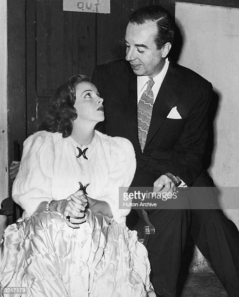 American actor Judy Garland listens to her husband American film director Vincente Minnelli while they sit together backstage at the Hollywood Bowl...