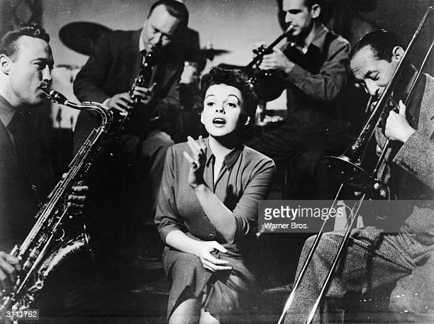 American actor Judy Garland sings with musicians on a bandstand in a still from the film 'A Star Is Born' directed by George Cukor 1954