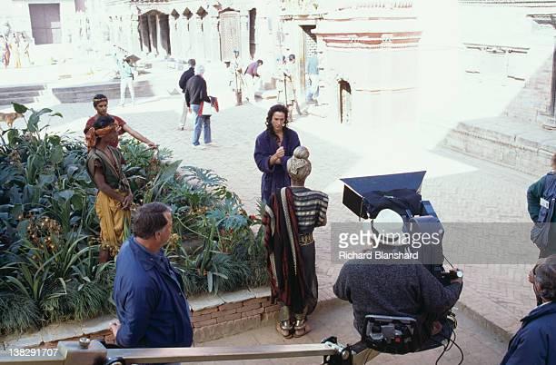 American actor Keanu Reeves on the set of the film 'Little Buddha' circa 1992 Director Bernardo Bertolucci is behind the camera