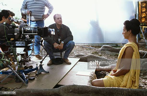 American actor Keanu Reeves watched by director Bernardo Bertolucci on the set of the film 'Little Buddha' circa 1992