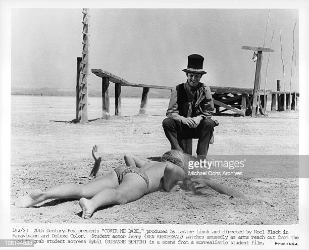 Ken Kercheval watches amusedly as arms reach out of from the sand to grab student actress Susanne Benton in a scene from the film 'Cover Me Babe'...