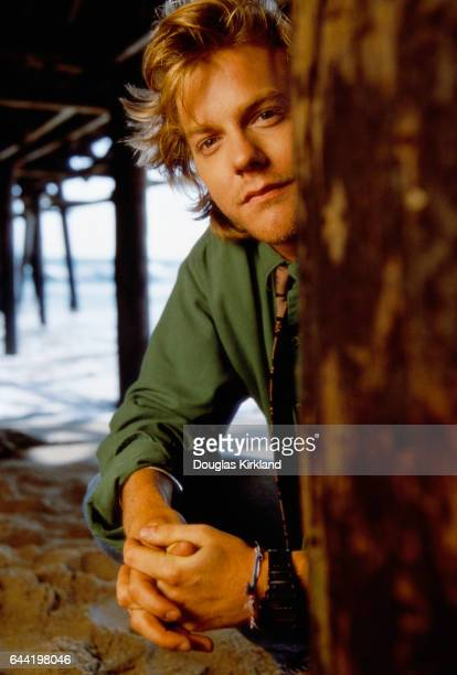 American actor Kiefer Sutherland clasps his hands as he squats under a pier