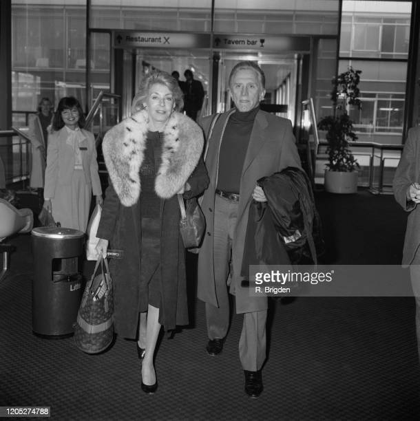 American actor Kirk Douglas and his wife Anne Buydens, wearing a fur collar, at Heathrow Airport in London, England, 10th March 1985.