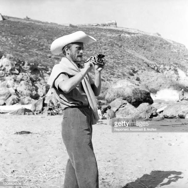 American actor Kirk Douglas , as Ulysses, taking a photo on the set of the film Ulysses. 1953