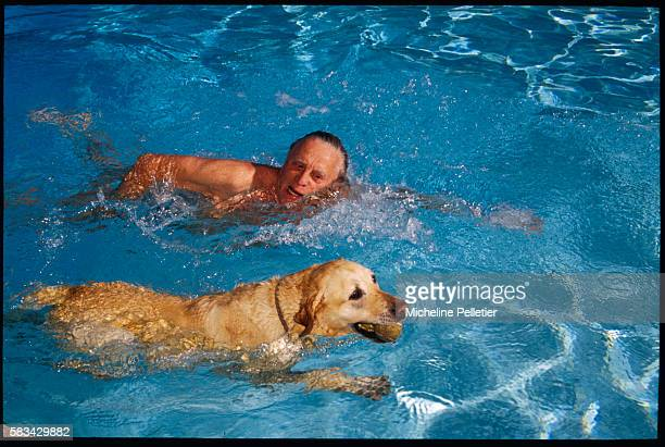 American actor Kirk Douglas enjoys a splash in the pool with his dog