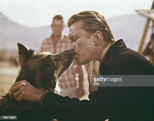 American actor Kirk Douglas kissing a German shepherd, circa 1962.