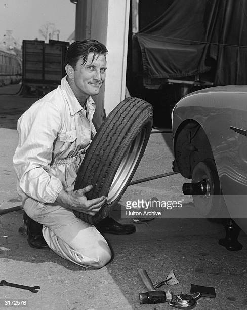 American actor Kirk Douglas kneels to change a tire on his AustinHealy during a break in the production of director Henry Hathaway's film 'The...