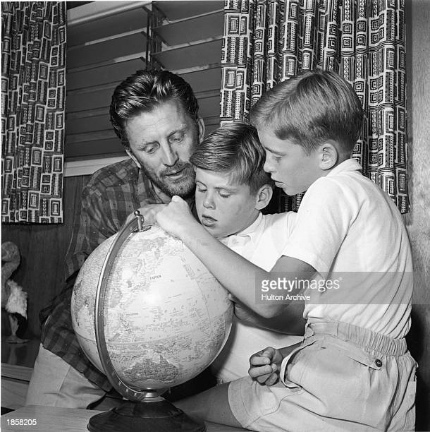 American actor Kirk Douglas looks at a world globe with two of his sons, Joel and Michael Douglas c. 1956.