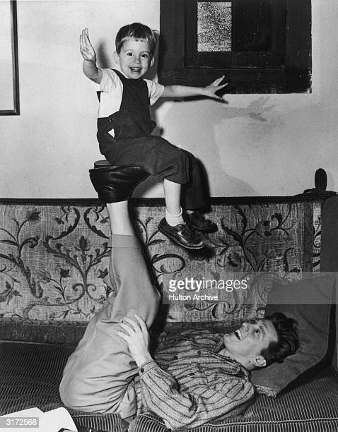American actor Kirk Douglas lying on a couch with his legs in the air as he balances his son, Michael on the soles of his feet.