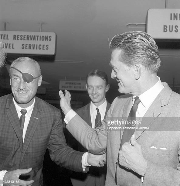 American actor Kirk Douglas patting a man with an eyepatch on his back at Fiumicino Airport. Rome, 7th October 1961