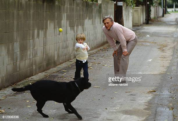 American actor Kirk Douglas plays with his grandson Cameron, the son of actor Michael and Diandra Douglas.