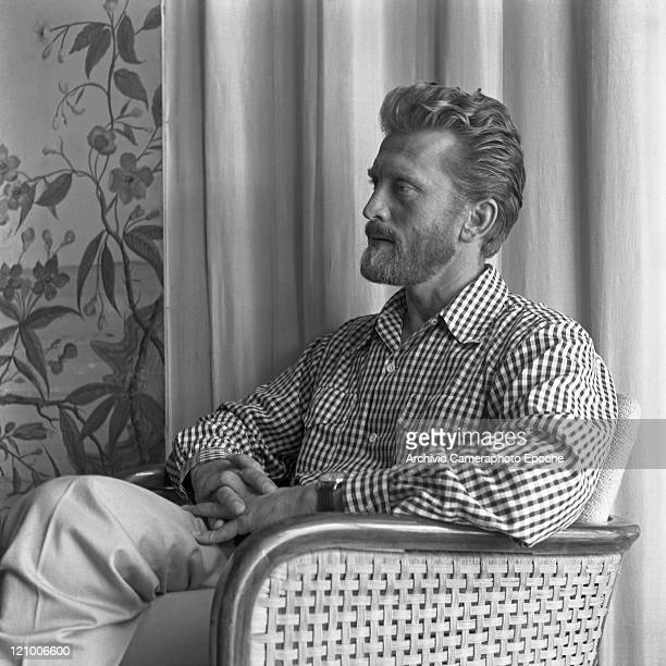 American actor Kirk Douglas portrayed from the side while sitting on a chair wearing a vichy shirt his fingers crossed Venice 1953