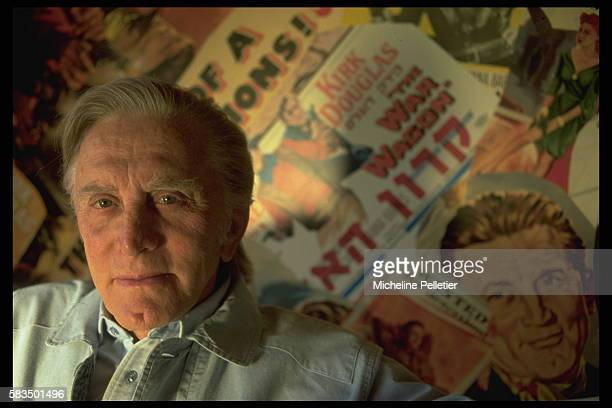 American actor Kirk Douglas relaxes at home in front of a wallsized collage of his film posters