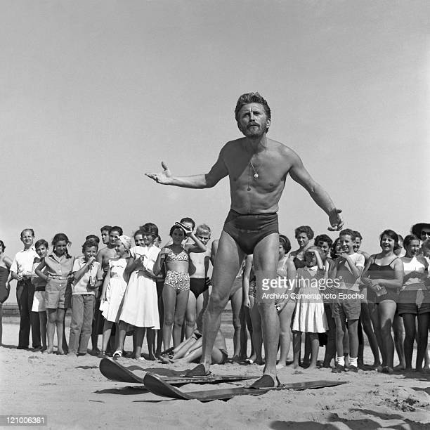 American actor Kirk Douglas wearing a swimming suit and a necklace chainlet portrayed while wearing a pair of waterski surrounded by kids fans on the...