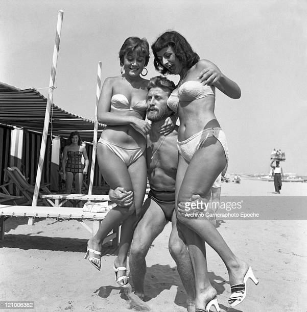 American actor Kirk Douglas wearing a swimming suit and a necklace chainlet portrayed while lifting two girls the paintress Novella Parigini and the...