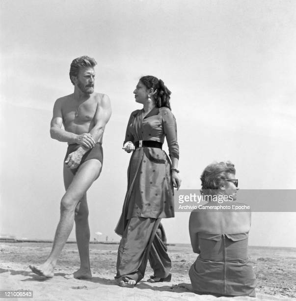 American actor Kirk Douglas, wearing a swimming suit and a necklace chainlet, walking on the seashore with an indian actress, Lido, Venice 1953.