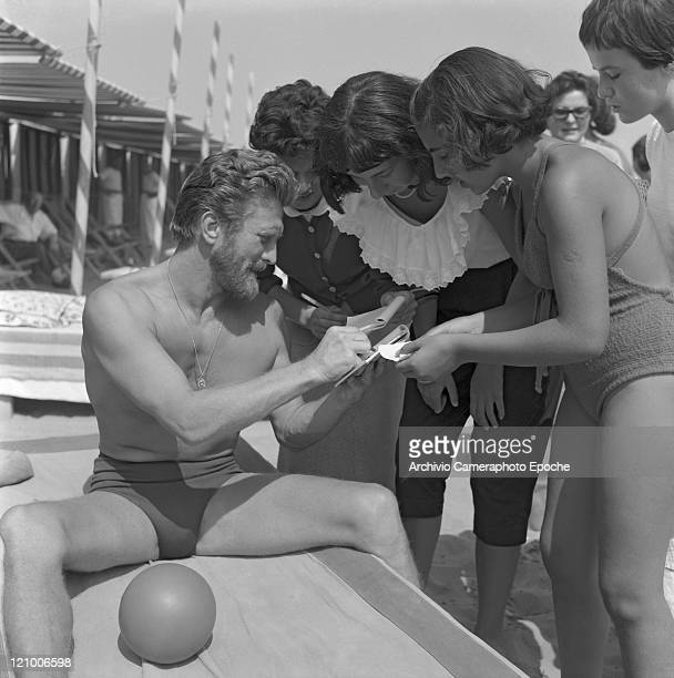 American actor Kirk Douglas, wearing a swimming suit and a necklace chainlet, sitting on a sunbed with a ball next to him, signing autographs to some...