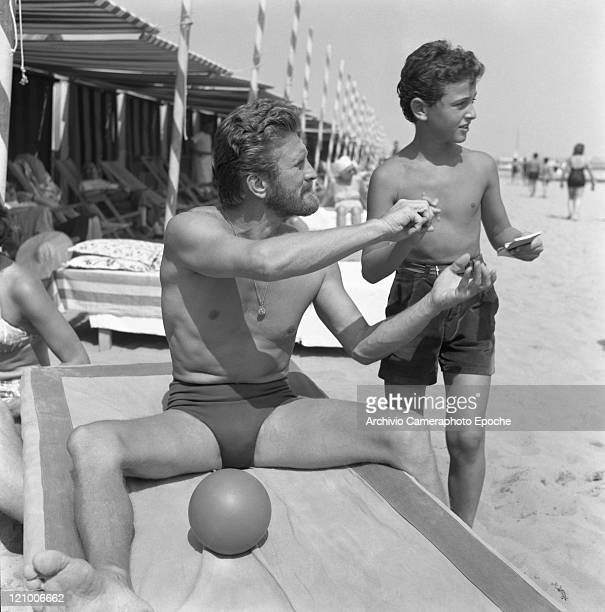American actor Kirk Douglas wearing a swimming suit and a necklace chainlet portraiyed while sitting on a sunbed a ball next to him making an...