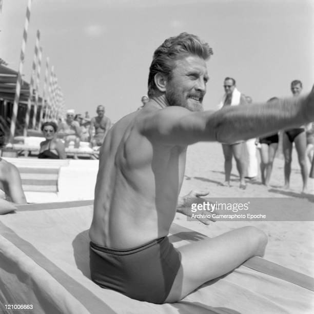 American actor Kirk Douglas wearing a swimming suit and a necklace chainlet portraiyed while sitting on a sunbed on the Lido beach Venice 1953
