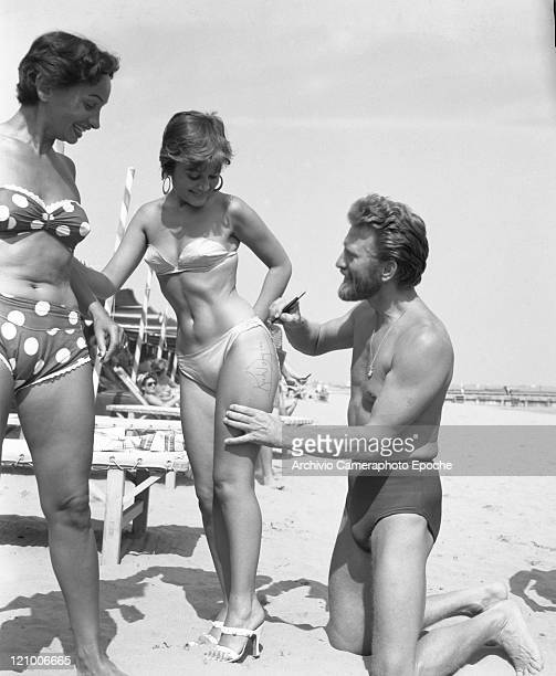 American actor Kirk Douglas, wearing a swimming suit and a necklace chainlet, signing on the thigh of the paintress Novella Parigini, wearing a...