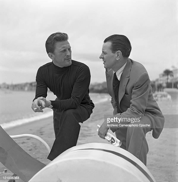 American actor Kirk Douglas, wearing a turtleneck sweater and smoking a cigarette, portrayed while talking to another man on the Lido beach, Venice...