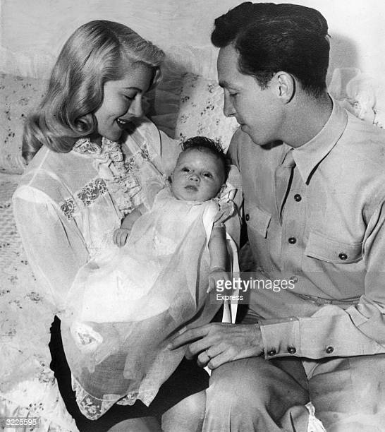 American actor Lana Turner smiles while holding her newborn daughter Cheryl Crane next to her second and third husband Stephen Crane Crane is wearing...