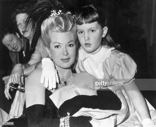 American actor Lana Turner wearing a period costume with a feather headdress sits with her daughter Cheryl Crane on the set of director Curtis...